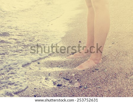 Vacation holidays.Feet closeup of relaxing on beach in sunny summer day. - stock photo