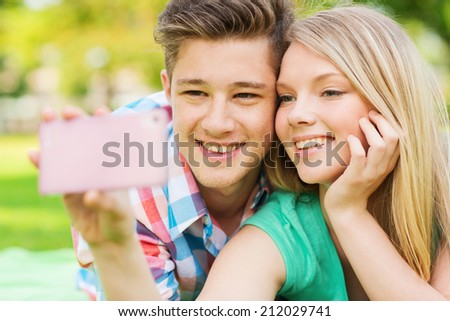 vacation, holidays, technology and friendship concept - smiling couple lying on blanket and making selfie with smartphone in park - stock photo