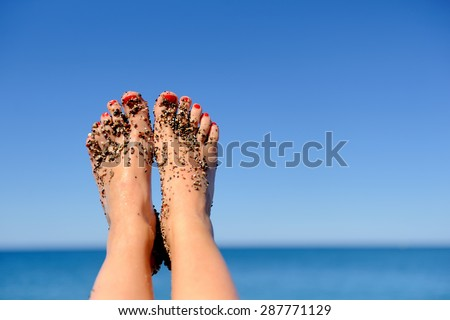 Vacation holidays. Woman feet closeup of girl relaxing on beach - stock photo