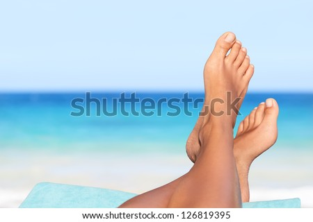 Vacation holidays. Woman feet closeup of girl relaxing on beach on sunbed enjoying sun on sunny summer day. - stock photo