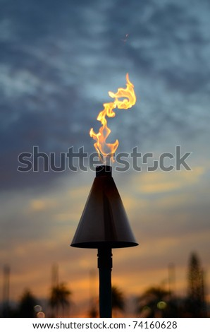Vacation Image Of A Hawaiian Tiki Torch At Sunset - stock photo