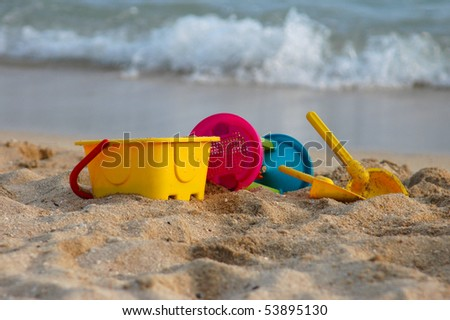 Vacation image of children's beach toys on the sand - stock photo