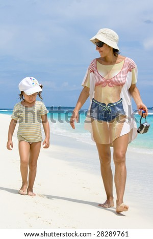 Vacation it is time to chat with child walking on the beach, it is time to relax and make family closer - stock photo