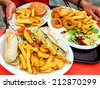 Vacation junk food lunch (fish and chips in ciabatta bread with melted cheese, hamburger and fried shrimps calamaris mix) at terrace of seaside restaurant in sunny day. Bretagne, France. - stock photo