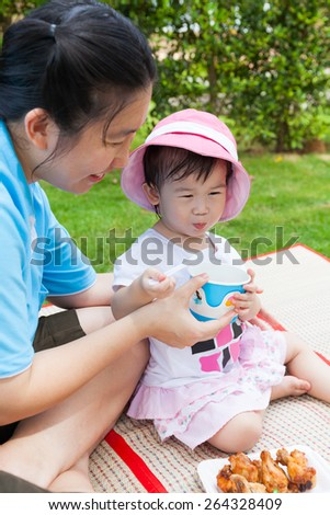 Vacation, mother and adorable little asian (thai) girl enjoy eating their lunch in the park, child holding spoon and cup, fried chicken on plate, over blur green nature background - stock photo