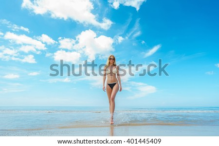 Vacation on the sea. Young sexy caucasian woman walk on ocean beach. - stock photo