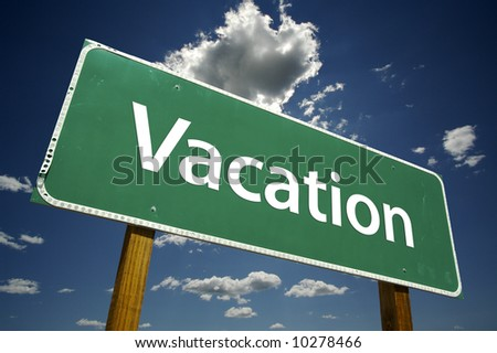 Vacation Road Sign with dramatic blue sky and clouds. - stock photo