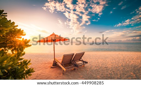 Vacation summer holidays background wallpaper - two beach lounge chairs under beach umbrella on beach, sunset mood. - stock photo