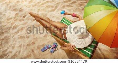 Vacation. Travel. Beautiful young woman relaxing on beach chair with cocktail. Top view - stock photo