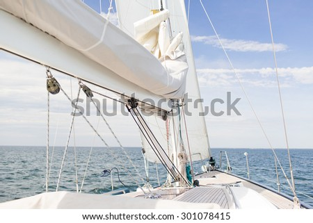 vacation, travel, cruise and leisure concept - close up of sailboat mast or yacht sailing on sea - stock photo