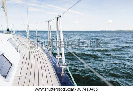 vacation, travel, cruise and leisure concept - close up of sailboat or sailing yacht deck and sea - stock photo