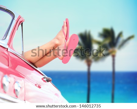 Vacation travel freedom beach concept with cool convertible vintage car and woman feet out of window against tropical see background with palm trees. Girl relaxing enjoying free holidays. - stock photo