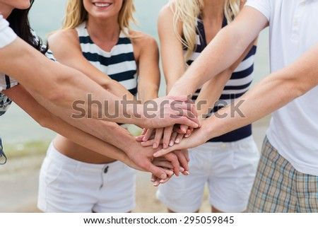 vacation, travel, sea, friendship and people concept - close up of happy friends with hands on top on beach