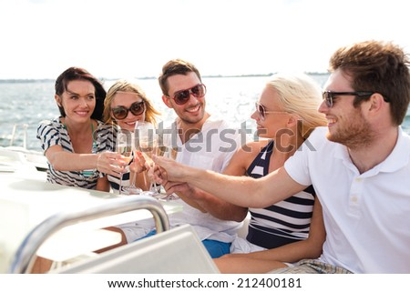 vacation, travel, sea, friendship and people concept - smiling friends with glasses of champagne on yacht - stock photo