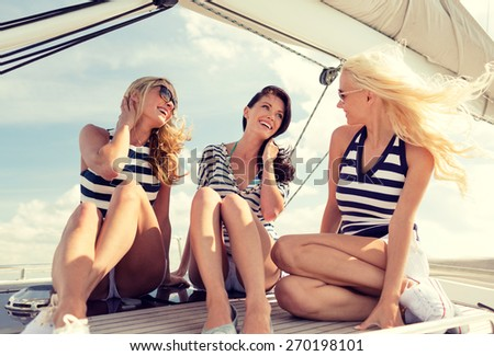 vacation, travel, sea, friendship and people concept - smiling girlfriends sitting on yacht deck - stock photo