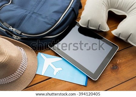 vacation, travel, tourism, technology and objects concept - close up of tablet pc computer and traveler personal stuff - stock photo