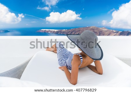 Vacation travel woman relaxing enjoying Santorini looking at famous view of Caldera. Young lady lying down on sun bed sofa lounge chair on holidays. Amazing view of sea. Europe travel destination. - stock photo