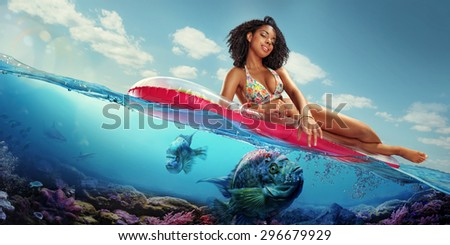 Vacation. Traveling. Woman hanging out on air mattress. With underwater part - stock photo
