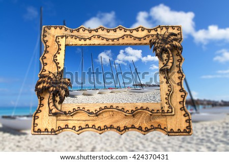 Vacation tropical hand made wooden picture frame on blurred background - stock photo