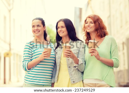 vacation, weekend, drinks and friendship concept - smiling teenage girls with coffee cups on street - stock photo