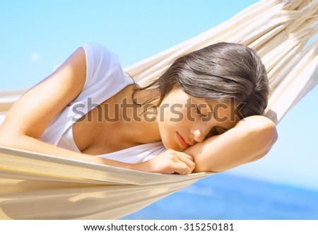 Vacation woman relaxing on beach in hammock on summer holidays resort - stock photo