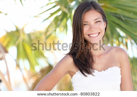 Vacation woman smiling on tropical beach summer holidays with palm trees. Portrait of pretty happy mixed race Caucasian / Asian female model. - stock photo