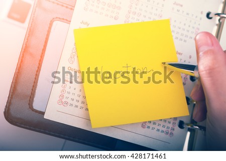 Vacation written on a memo at the office  - stock photo