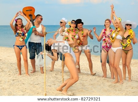 Vacationers have fun doing the limbo - stock photo