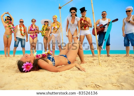 Vacationers have fun doing the limbo. One from them falling down - stock photo