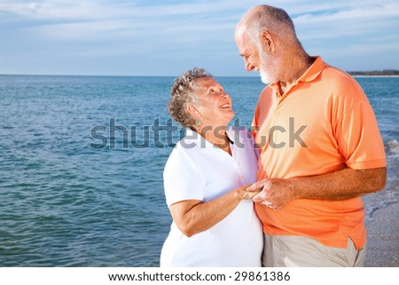 Vacationing senior couple gets romantic at the beach.