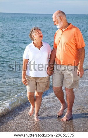 Vacationing senior couple takes a romantic stroll on the beach. - stock photo