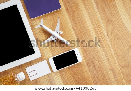 vacations and technology concept - close up of tablet pc, smartphone, passport, simcard on wooden desk - stock photo