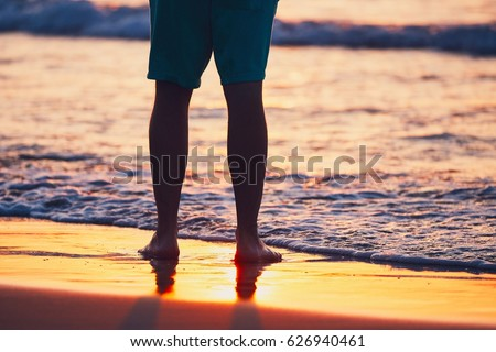Vacations on the idyllic beach. Legs of the young man during amazing sunset.