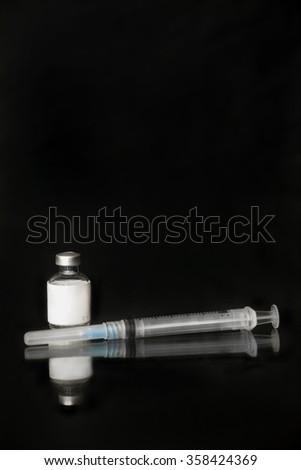 Vaccination vial and vaccine needle on black with reflection below - stock photo