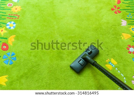 Vacuum cleaner cleans carpet, with copy space for text message, advertising - Spring Cleaning Concept - stock photo
