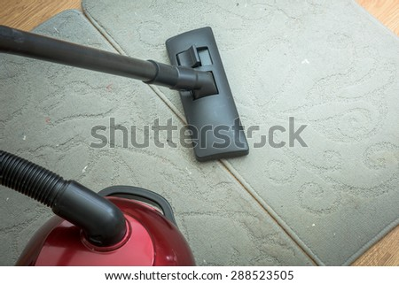 Vacuum cleaner on a gray carpet. Housework