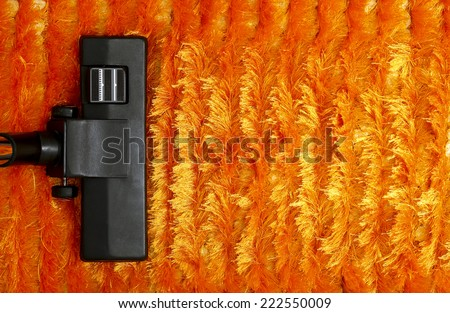 vacuum cleaner on orange fluffy carpet  - stock photo