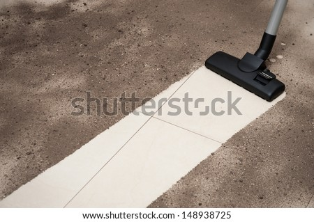 Vacuum cleaning dirt on a tiled floor - stock photo