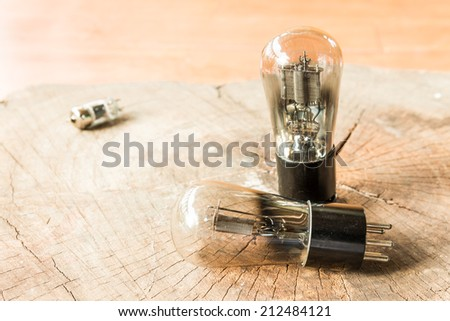 Vacuum electronic preamplifier tubes on old wood background. - stock photo