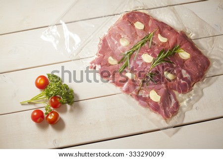Vacuum packed lamb meat with garlic and baby tomatoes on white wooden table - stock photo