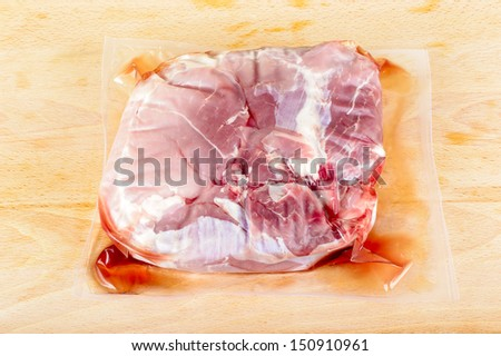 Vacuum packed pork meat on wooden cutting board. - stock photo