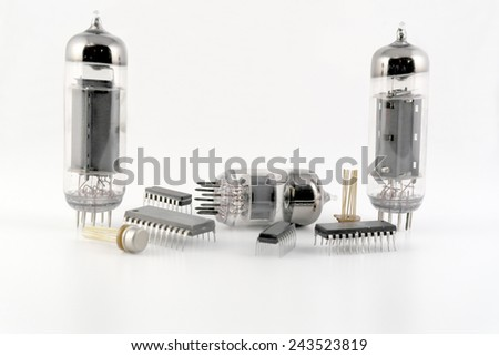 Vacuum radio tubes and semiconductor chips over white - stock photo