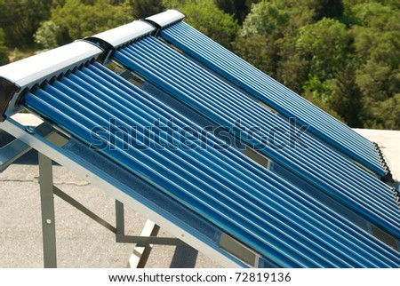 Vacuum solar water heating system on the house roof. - stock photo