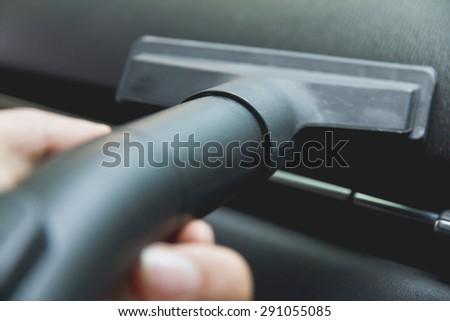 Vacuuming car interior - stock photo