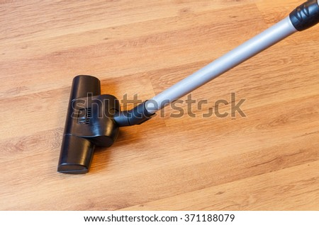 vacuuming of parquet floor by vacuum cleaner at home - stock photo