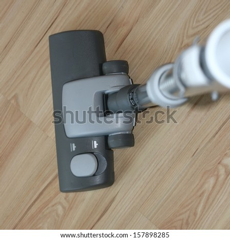 vacuuming wooden floor  - stock photo