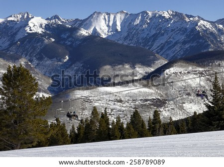 VAIL, CO - FEBRUARY 9: Skiers ride a chairlift at Vail Mountain in Vail, Colorado on February 9, 2015. Vail Mountain is located in the White River National Forest and is home of the Vail Ski Resort. - stock photo