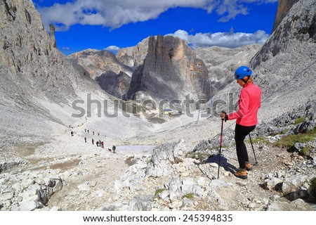 Vajolet towers and distant refuge in front of via ferrata climber, Catinaccio massif, Dolomite Alps, Italy - stock photo