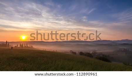 Val d'Orcia after sunrise with photographer, Tuscany, Italy - stock photo