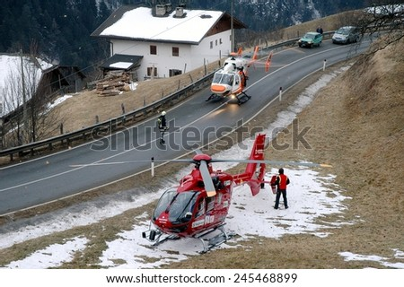 VAL GARDENA, ITALY - JANUARY 20, 2015: Two Helicopters ready to take off to save and transport a seriously injured person to hospital after hard car accident on the iced road on January 20, 2015 - stock photo
